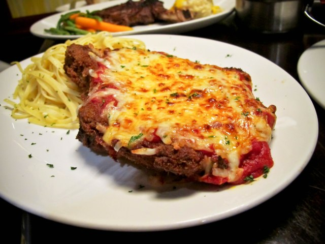 Pork Cutlet Parmesan -  Bone-in Rib Chop with Mozzarella  and Tomato Sauce over Pasta Aioli ($25)